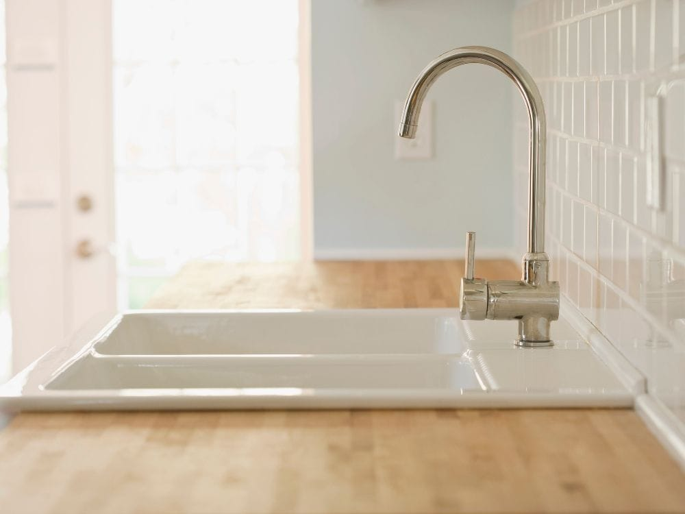 top mount farmhouse sink installed on wood countertop
