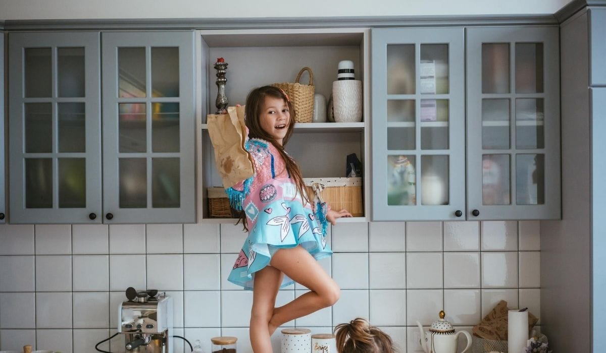 little girl looking for cookie in pantry