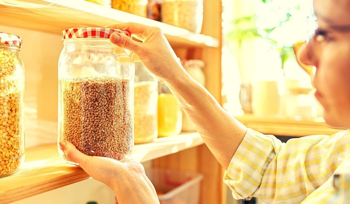 woman holding and organizing jar in pantry