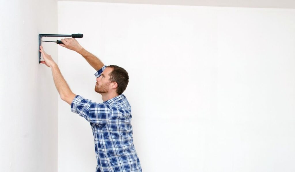 Young man installing shelves
