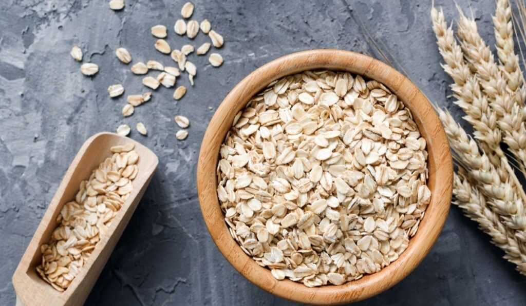 rolled oats in a wooden bowl on a stone background