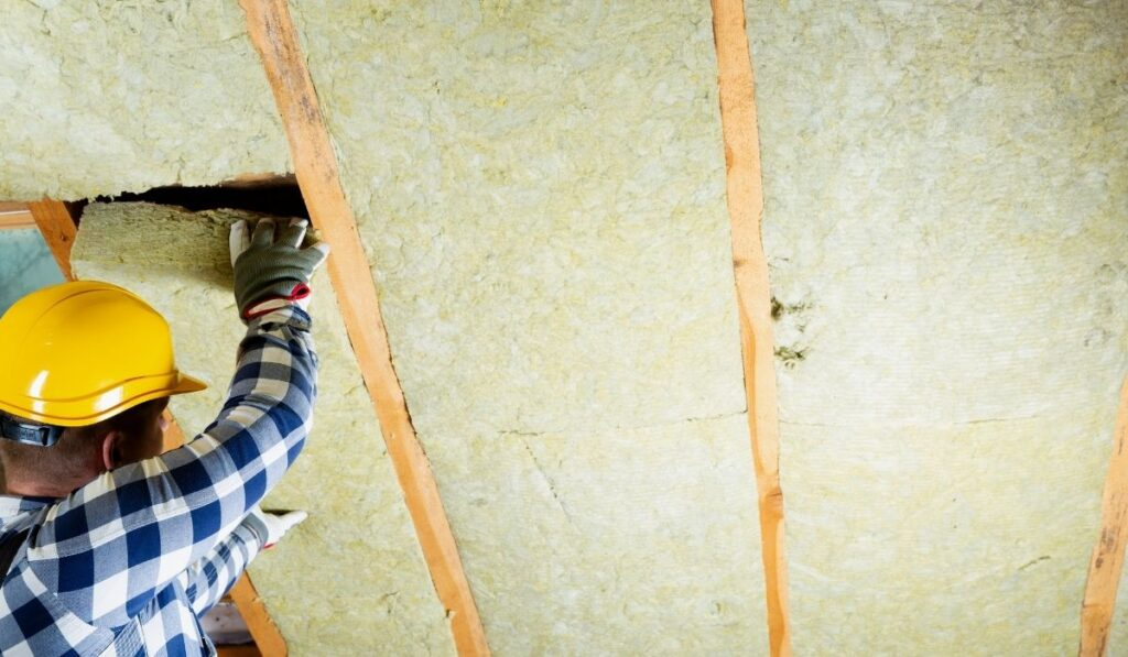 Man Installing Thermal Insulation Layer At The Attic