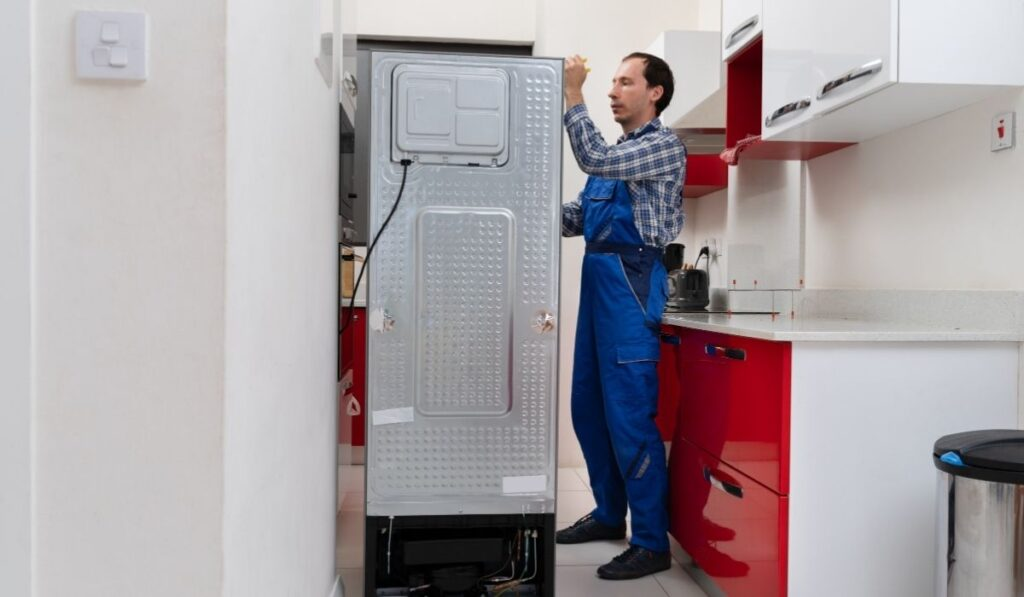 Serviceman working on fridge