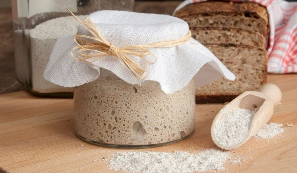 sourdough starter in a cute covered glass with some sliced breads on the wooden table