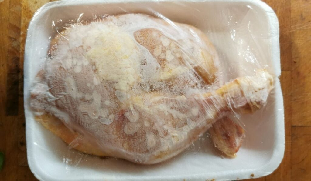 whole frozen chicken in a styrofoam