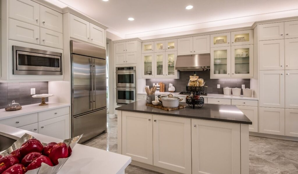 white kitchen with pantry cabinet beside the oven