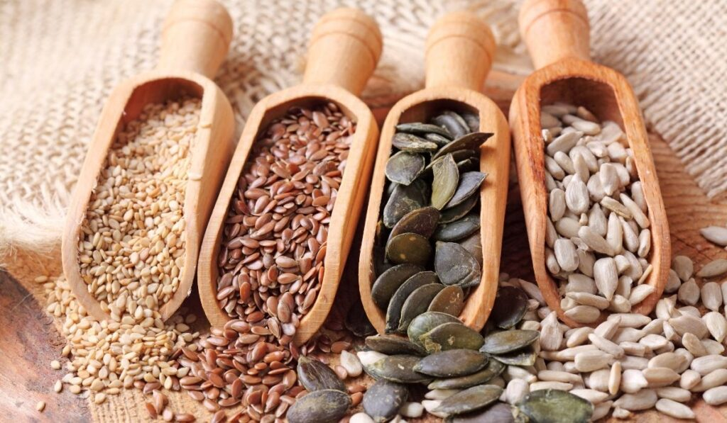 sesame, flax, pumpkin and sunflower seeds in wooden scoops
