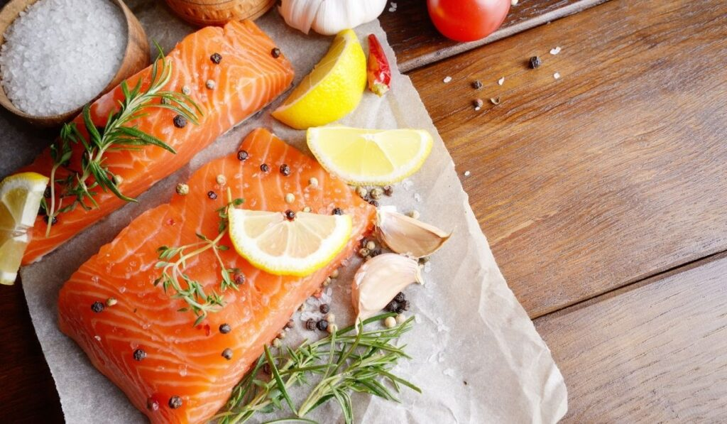 raw salmon on baking paper with garlic, lemon, and some herb and spices