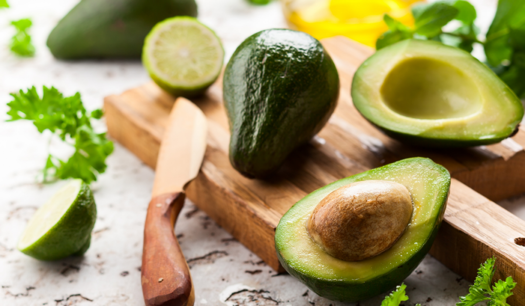 An avocado and a sliced avocado on w wooden chopping board with wooden knife beside it.
