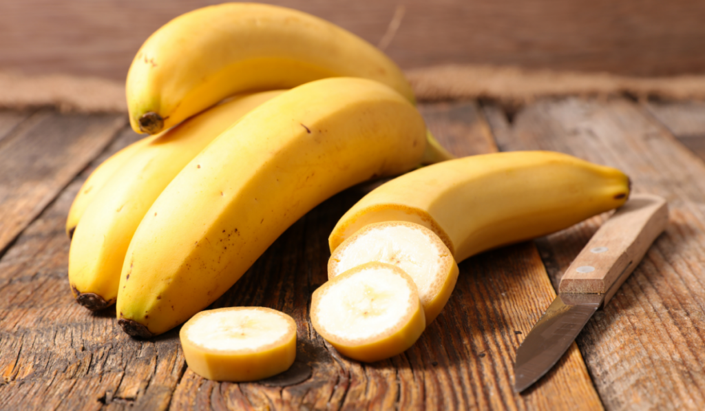 Bananas on a wooden table with a knife on the side.