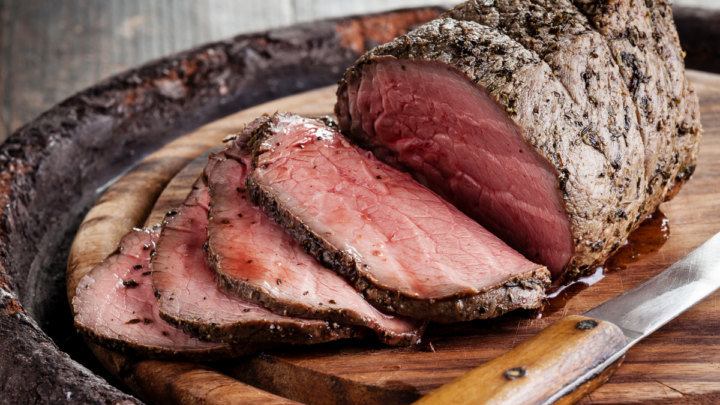 A juicy roast beef on a chopping board with knife.