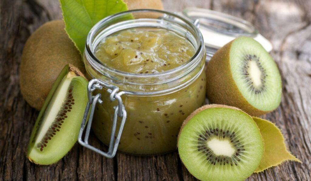 kiwi jam in a clear jam and fresh kiwi around it