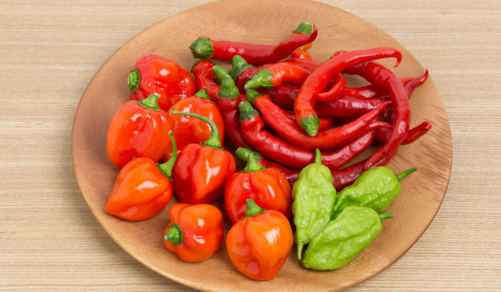 Different type of peppers on a wooden plate